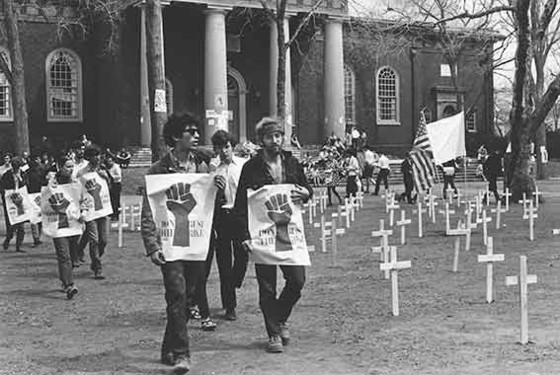 View of a student protester wearing a T-shirt with the logo designed by Harvey Hacker, on Harvard Yard, Harvard University, Cambridge, Massachusetts, 1969. Photo: Daniel S. Brody