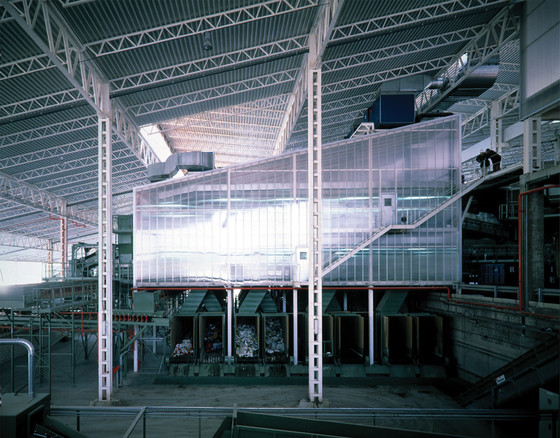 Ábalos Herreros, Recycling Plant for Urban Waste, Madrid, Spain, 1999. The plant is located on historically arid, degraded land used for dumping waste. It is part of a larger project to convert the existing landfill area into a regional park. Its design and colors mimic the local topography, whereas site selection and building orientation adapt to a hill in order to utilize gravitational systems for selection, movement, and processing of waste. Everything is made with prefabricated industrial beams and the building is wrapped in recycled polycarbonate. The plant has a designated compost section, and also takes advantage of organic material by reusing it as construction material for the green roof. A visitor center/museum area allows visitors to observe how waste moves around the plant. The central building can be recycled and reused as a service building for the planned regional park along the Manzanares River, or dismantled to produce recyclable components/materials.